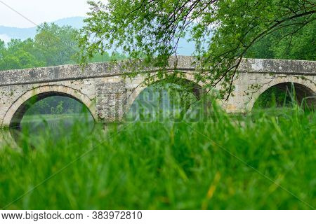 Rimski Most Or Roman Bridge Reflecting In The Bosna River During Haze. Famous Touristic Attraction A