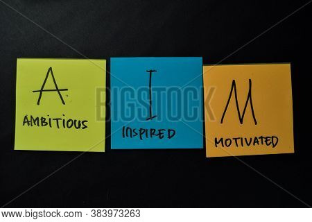 Aim - Ambitious Inspired Motivated Write On Sticky Notes Isolated On Office Desk.