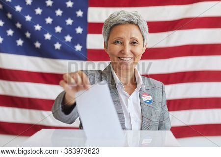Portrait Of Smiling Senior Woman Putting Vote Bulletin In Ballot Box And Looking At Camera While Pos