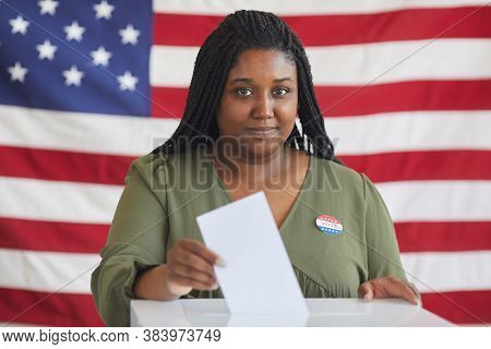 Portrait Of Young African-american Woman Putting Vote Bulletin In Ballot Box And Looking At Camera W