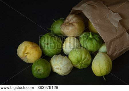 Tomatillos Spilling From A Paper Bag That Is Turned Over, On Black Background, Viewed From Dinner An
