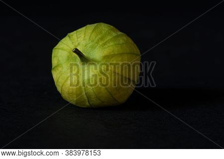 Unwashed Green Tomatillo On Black Background, Viewed From Dinner Angle- California Produce Concept
