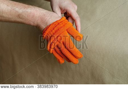 The Man Takes Off His Orange Work Gloves. End Of The Working Day. Selective Focus.