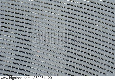 Abstract Geometric Background. Gray Plastic Perforated Surface. Curved Lines Of Repeating Holes. Sel