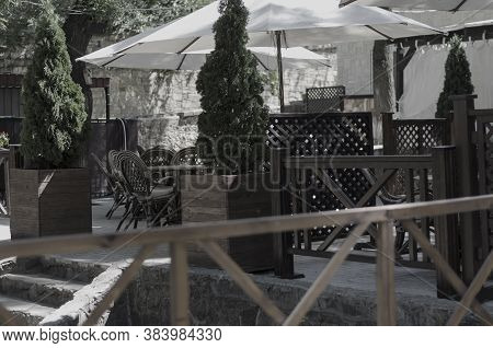 Empty Summer Terrace Of The Restaurant. Sunny Outdoor Terrace With Rattan Furnitures. Sunny Day With