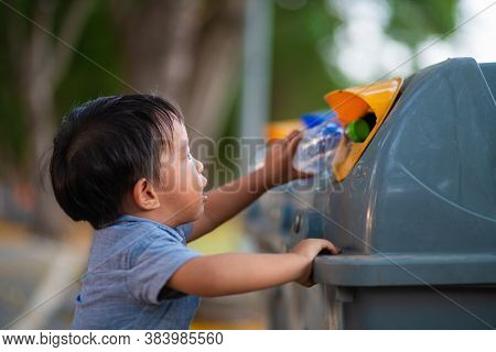 Little Asian Toddler Baby Boy Throwing Plastic Bottle In Recycling Trash Bin At Public Park