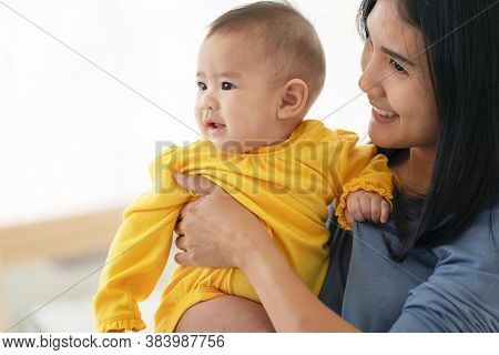 Thai Mum Is Comforting A Baby. Woman Holding A Newborn Baby In Her Arms