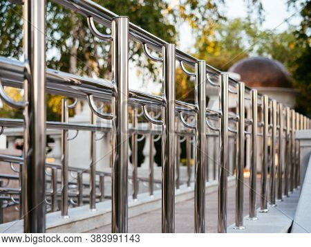 Chrome-plated Metal Railing In The Park. Ramp For Disabled People And Wheelchairs. Background With B