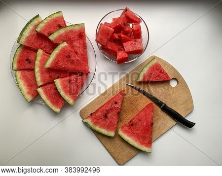 The Process Of Slicing Watermelon. Fresh Slices Of Watermelon On A Wooden Board, Transparent Plate A