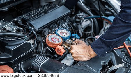 Auto Mechanic Are Using Measuring Equipment Tool For Filling Car Air Conditioners. Concepts Of Car C