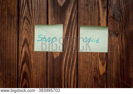 Two Streakers With The Words Stop Covid. Wooden Background With A Beautiful Texture. Advertising Pos