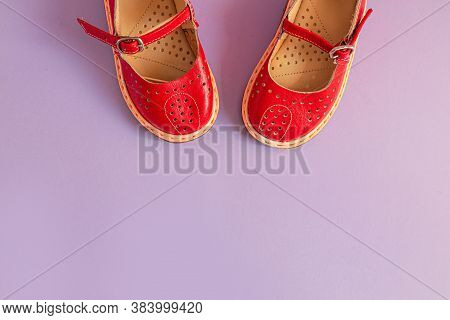 Bright Red Kids Shoes On Lilac Background With Copyspace. Baby Clothes Concept. Top View, Flat Lay