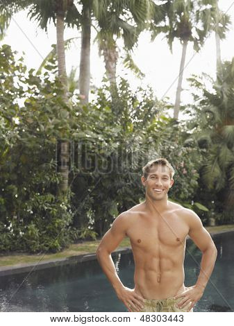 Portrait of a shirtless macho young man smiling by swimming pool