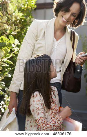 Happy woman with daughter holding handbags in frontyard