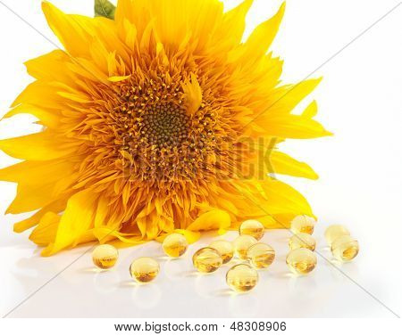 The sunflower and capsules with vitamins A and E on foreground poster