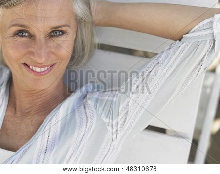 Closeup portrait of a smiling middle aged woman reclining on sunlounger