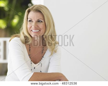 Smiling middle aged woman sitting on verandah and looking away