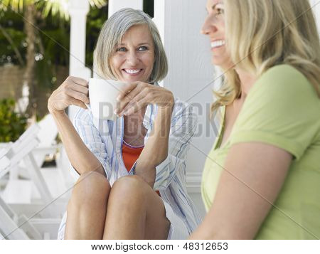 Two happy middle aged women sitting on verandah with coffee cup