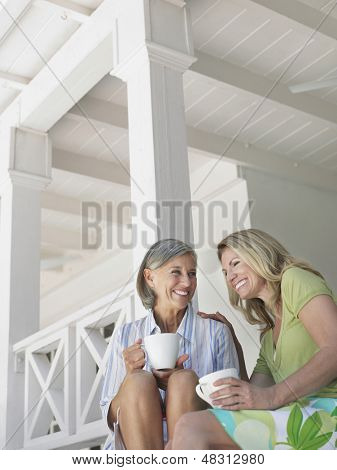 Two happy middle aged women sitting on verandah with coffee cups