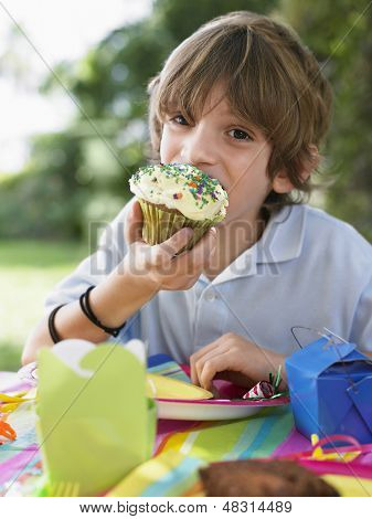 Portrait of little young boy eating cupcake at the outdoor birthday party