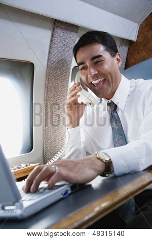 Businessman using telephone on private airplane