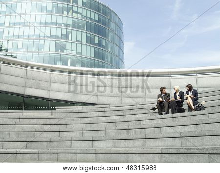 Full length of three business people sitting on steps outside office building during lunch break