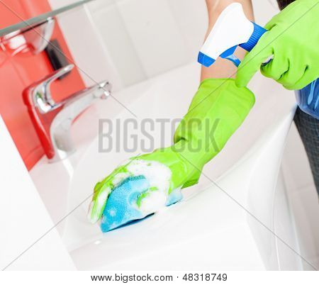 Woman cleaning sink and faucet in bathroom at home