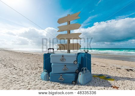 Pile of luggage and directional signs pointing everywhere in a tropical beach