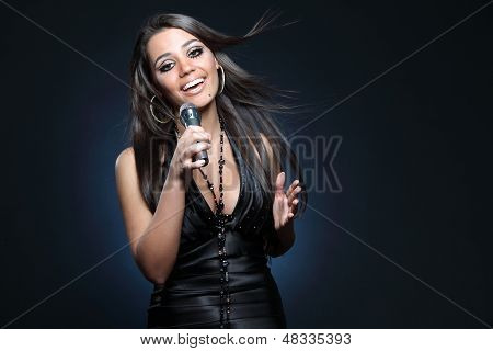 studio shot of a beautiful young singer on dark background poster