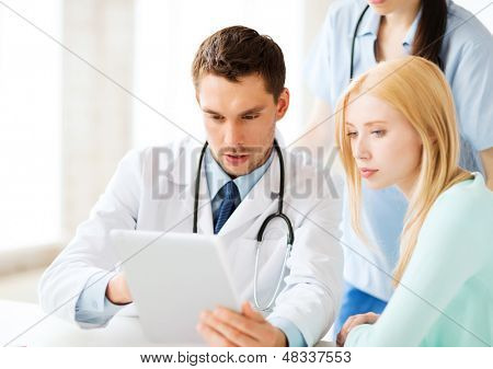 healthcare, medical and technology - doctor showing something patient on tablet pc in hospital