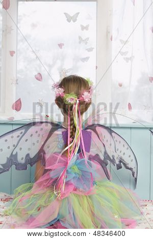 Rear view of a young girl in fairy costume looking through window