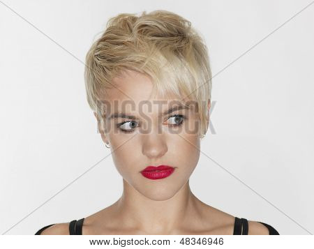 Closeup of beautiful young woman with red lips looking sideways on white background