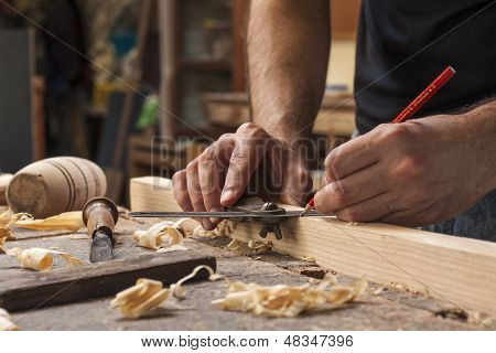 hand of a carpenter taking measurement of a wooden plank poster