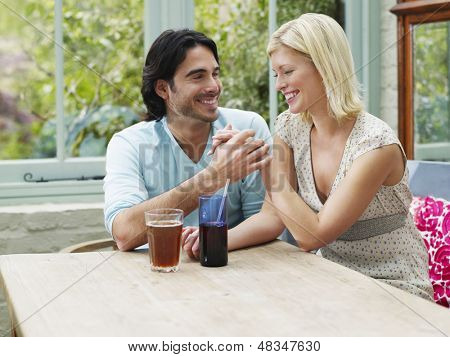 Cheerful young multiethnic couple holding hands at verandah table