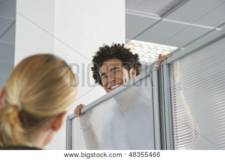 Smiling male office worker peering over cubicle wall to greet blond coworker in office