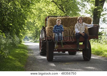 Full length portrait of two young boys sitting on back of trailer on country lane