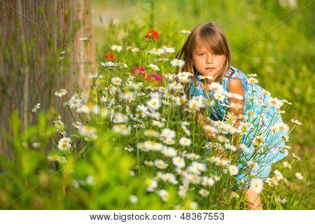 Charming little girl among yellow wildflowers