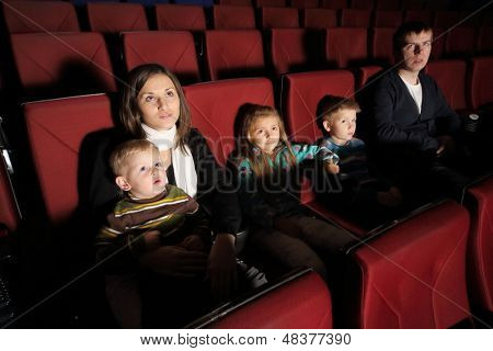Parents with their children watching a movie in the cinema