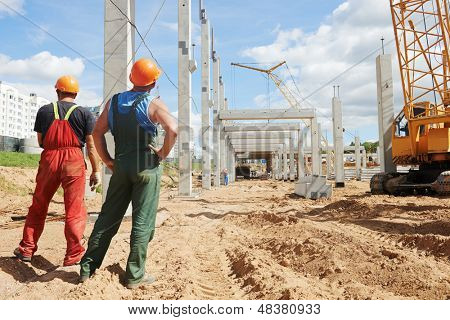 two builder workers at construction site during concrete pole and beam installation poster