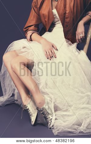 portrait of untraditional bride with tulle wedding dress wearing sequin shoes and leather jacket sitting against a purple background with retro effect