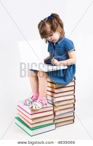 Photo of schoolgirl sitting on books and learning how to use laptop poster