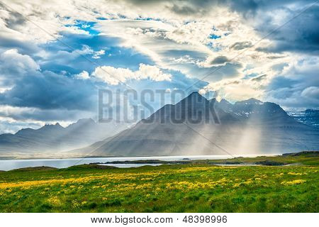 Sun is shining through the clouds on the fjord on the Iceland poster