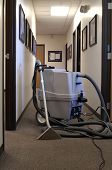 a steam carpet cleaning machine in a long office hallway poster