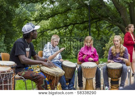 Black Musician From Africa Demostrates How To Play The Drums To Local Children
