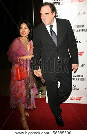 Oliver Stone and friend at the 21st Annual American Cinematheque Award Honoring George Clooney. Beverly Hilton Hotel, Beverly Hills, CA. 10-13-06