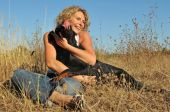 young smiling woman and her dog: purebred beauceron in a field poster