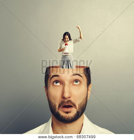 amazed businessman with open head. young emotional businesswoman standing into the head, looking at the man and screaming with megaphone. photo over grey background