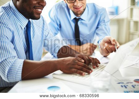 Image of two young businessmen discussing computer project at meeting