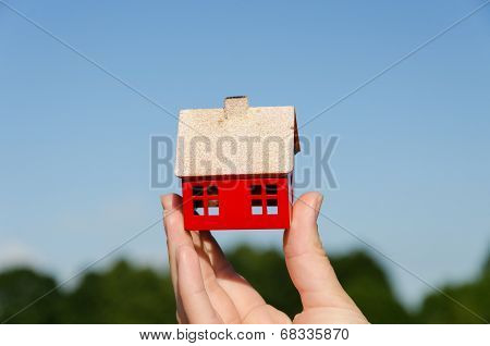 Hand Hold House Miniature On Blue Sky Background