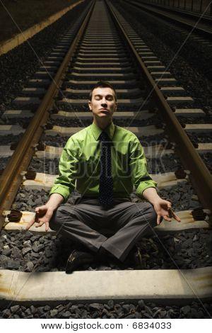Businessman Meditating On Railroad Tracks.